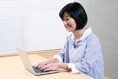PCに向かう中年女性