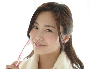 歯ブラシを持った笑顔の女性