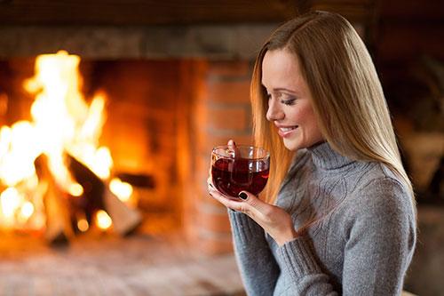 暖炉の近くでお茶を飲む女性